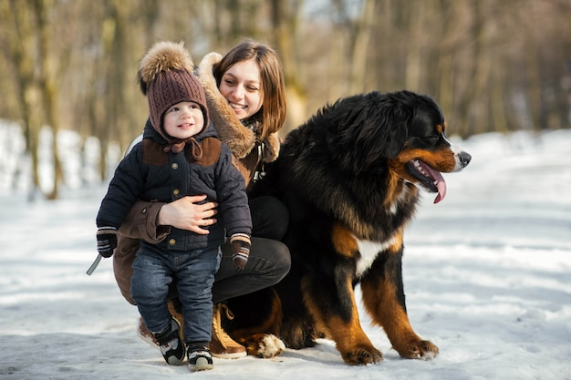 Woman hugs little boy and strokes bernese mountain dog posing in the park