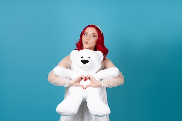 Woman hugs a white teddy bear, makes a heart symbol out of her fingers and blows a kiss