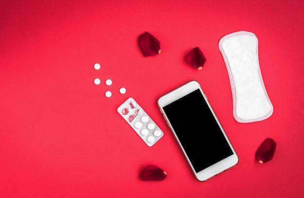 여성 위생 보호 또는 장미 꽃잎과 빨간색 배경에 휴대 전화 위생 패드. 월경주기 추적.
