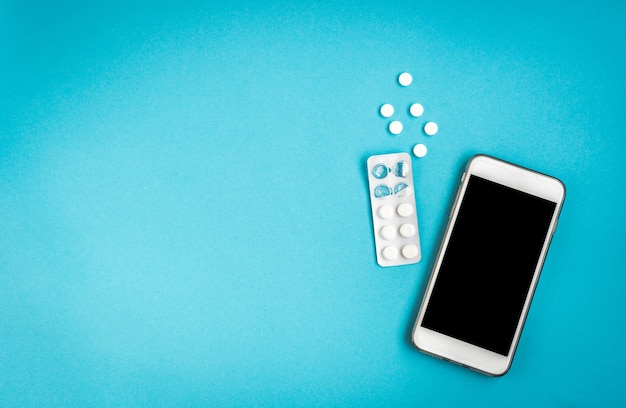 여성 위생 보호. 위생 패드와 파란색 배경에 휴대 전화입니다. 월경주기 추적.