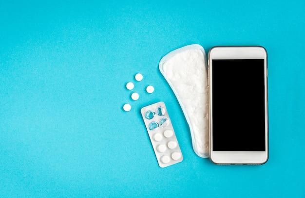 여성 위생 보호. 파란색에 위생 패드와 휴대 전화.