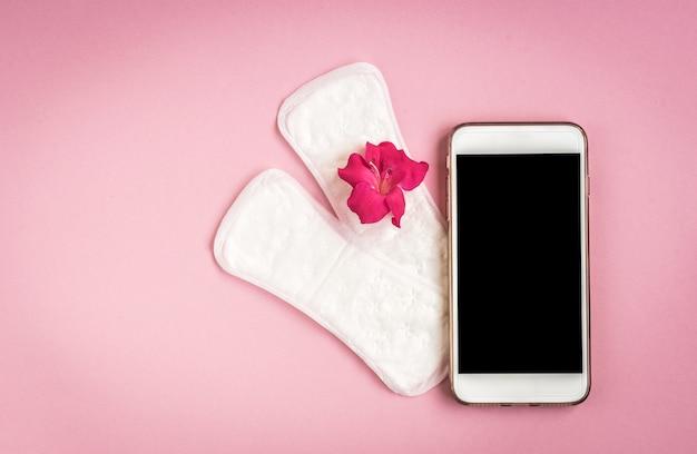 여성 위생 보호. 통증 약, 핑크 로즈와 분홍색 배경에 휴대 전화 위생 패드. 월경주기 추적.