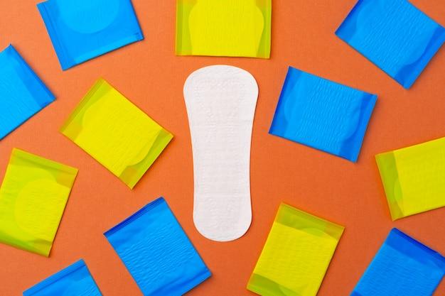 Женские гигиенические прокладки на оранжевом фоне, вид сверху, плоская планировка