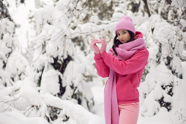 冬の雪に覆われた森の中で、ピンクの服を着て、ジャケット、ニットのスカーフ、帽子をかぶった手でハートを作った女性
