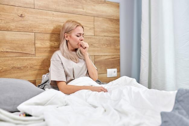 一人でベッドに座って、喉の痛みを抱えている自宅でインフルエンザにかかっている女性。季節性感染症インフルエンザアレルギーと鼻水を伴う病気の白人女性。コロナウイルス、covid-19および医学、ヘルスケア