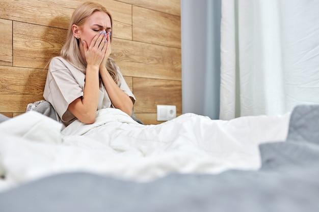 自宅でインフルエンザにかかっている女性が、ベッドに一人でくしゃみをして、喉の痛みを感じています。季節性感染症インフルエンザアレルギーと鼻水を伴う病気の白人女性。コロナウイルス、covid-19