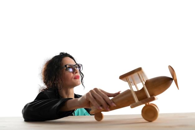 Женщина представляет, что улетает с деревянным игрушечным самолетиком