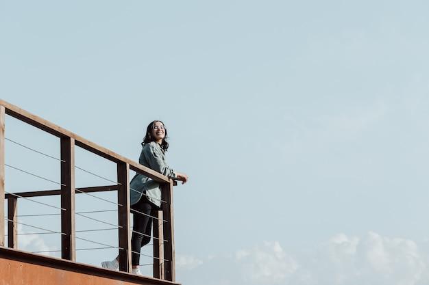 순간 자유와 자유 개념을 살고있는 거대한 강과 산 위에 발코니에있는 여자