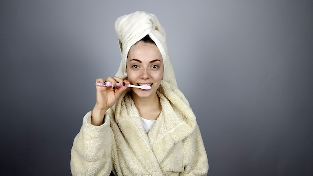 Женщина в халате чистит зубы