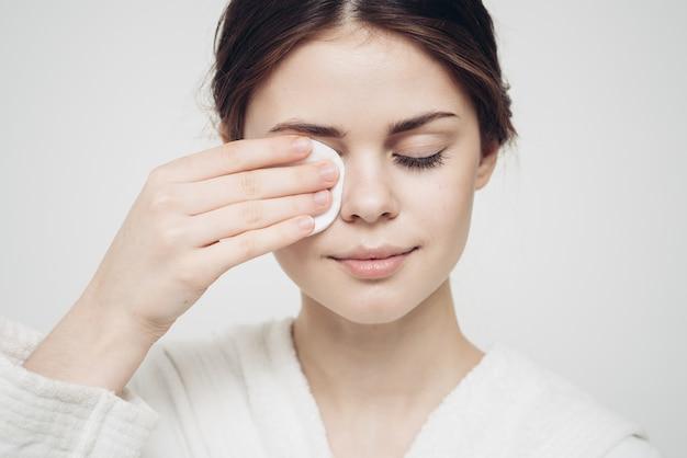 バスローブを着た女性が白いスポンジの外観ケア美容で顔を拭きます。高品質の写真