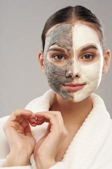 彼女の顔のスキンケアの若返りにマスクとバスローブを着た女性