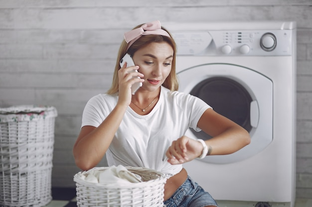 Женщина в ванной возле стиральной машины