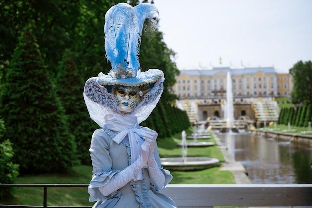 아름다운 푸른 카니발 드레스와 화창한 날 공원에서 베네치아 마스크의 여자