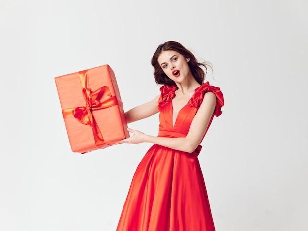 Женщина в красивом платье с подарочными коробками в студии, распродажи и торжества