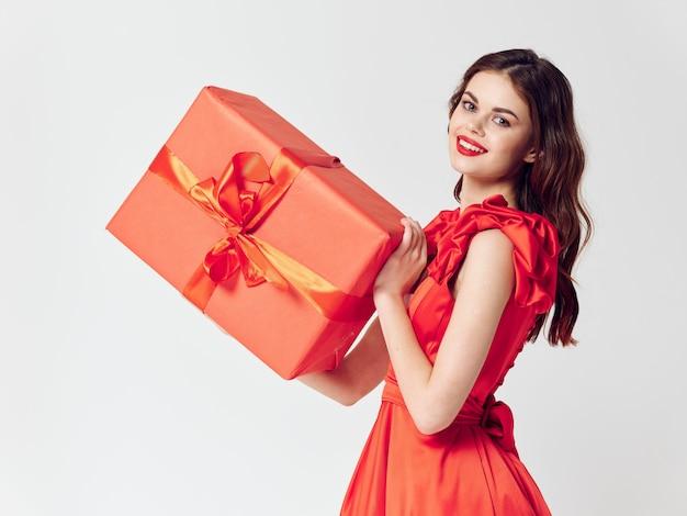 Женщина в красивом платье с подарочной коробкой, распродажей и торжеством