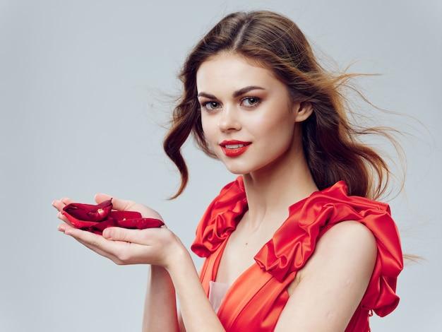 장미와 장미 꽃잎을 가진 아름 다운 빨간 드레스에 여자