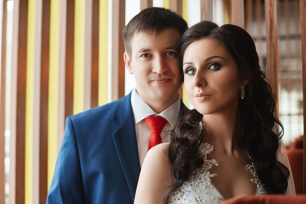 Женщина в красивом белом платье и мужчина в голубом костюме обнимаются возле окна. любящая и ласковая пара