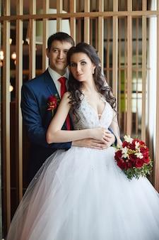 美しい白いドレスを着た女性と青いスーツを着た男性が窓の近くで抱きしめています。愛情のこもったカップル