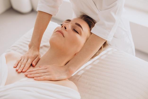 顔と首のマッサージをしている美容院の女性