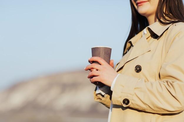 Женщина в бежевом пальто с бумажным стаканчиком в руках