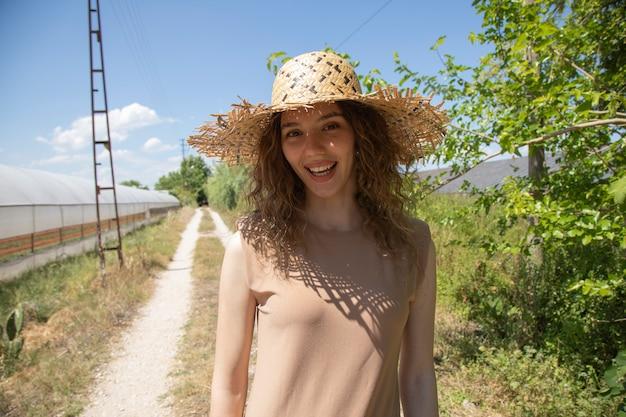 ベージュのドレスと田舎道でポーズ麦わら帽子の女性