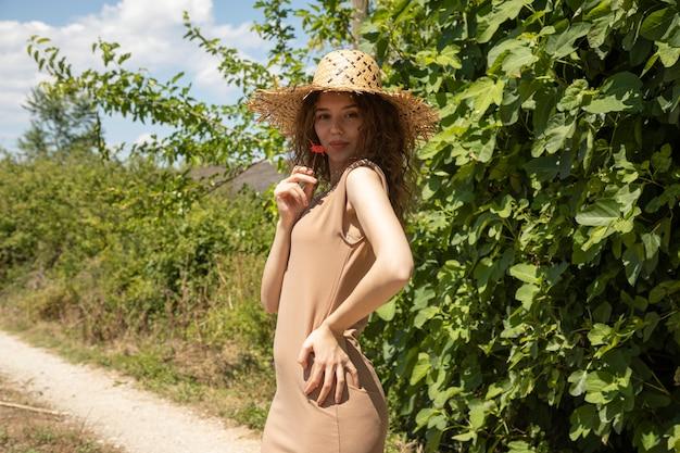 ケシの花でポーズベージュのドレスと麦わら帽子の女性