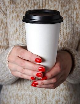 コーヒーの紙コップを保持しているベージュのセーターの女性