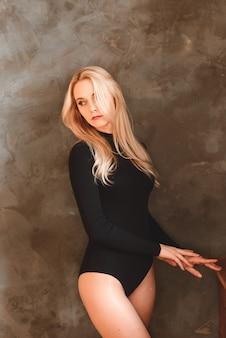 검은 bodysuit에서 여자입니다. 스튜디오에서 포즈 관능적 인 화려한 젊은 아가씨