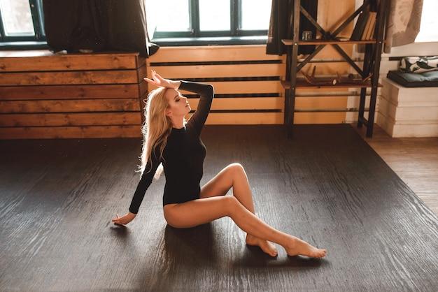 黒のボディースーツを着た女性。スタジオでポーズをとる官能的なゴージャスな若い女性