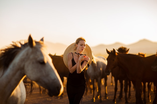 Женщина в черном платье среди диких лошадей