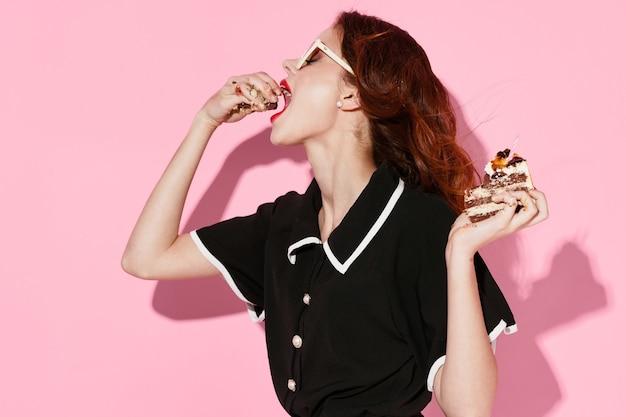 ケーキを食べる黒のドレスとメガネの女性