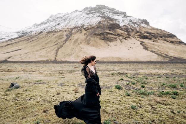 雪山でポーズをとって黒いドレスを着た女性。アイスランドの風景