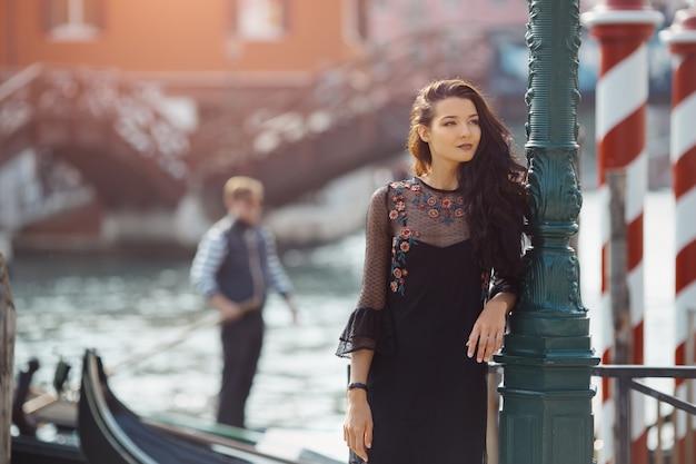 부두에 서있는 검은 드레스 여자