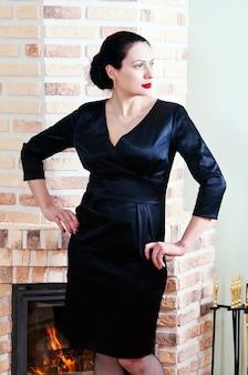 벽난로와 인테리어에 포즈 검은 이브닝 드레스에 여자 프리미엄 사진