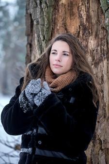공원에서 겨울에 검은 모피 코트를 입은 여자