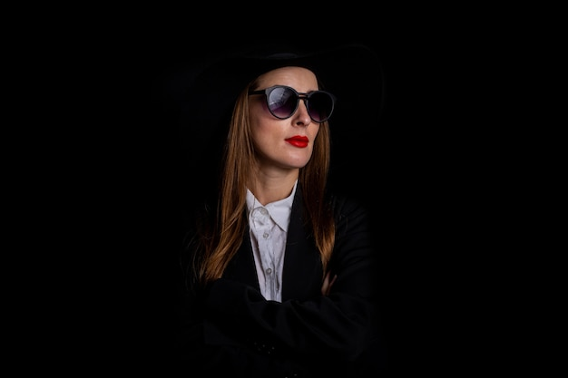 Женщина в черной шляпе, очках и куртке на черном.