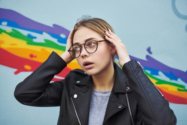 通りの色とりどりの壁のポーズで眼鏡をかけた黒いジャケットの女性