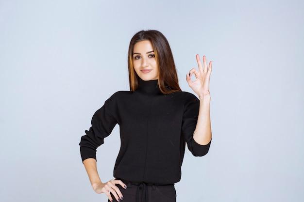 楽しみのサインを示す黒いシャツを着た女性。
