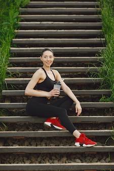 계단에 서있는 검은 spoerswear에 여자