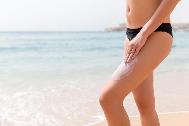 검은 수영복에 여자는 바다 배경에서 그녀의 다리에 그녀의 손가락으로 썬 크림을 적용하고 있습니다.