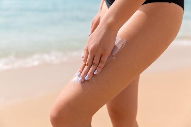 검은 수영복을 입은 여성이 해변에서 그녀의 다리에 손가락으로 태양 보호를 적용하고 있습니다.