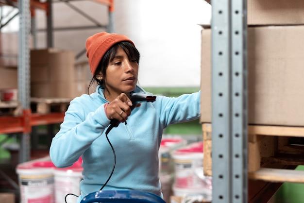 Женщина в синей блузке работает на складе