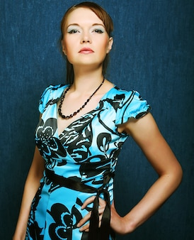 青い背景にポーズをとって青いドレスを着た女性