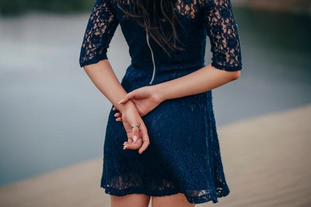 물 근처에 서 있는 파란 드레스를 입은 여자