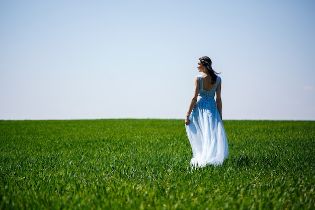 Женщина в голубом длинном платье на фоне зеленого поля. модный портрет красивой девушки с улыбкой на лице