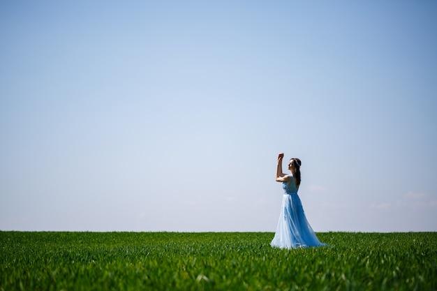 緑のフィールドの背景に青いロングドレスの女性。彼女の顔に笑顔で美しい少女のファッションの肖像画