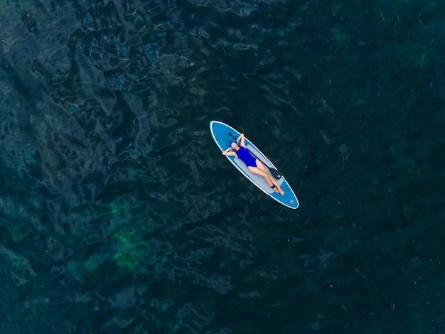 Женщина в синем купальнике лежит спиной на ужине далеко в море