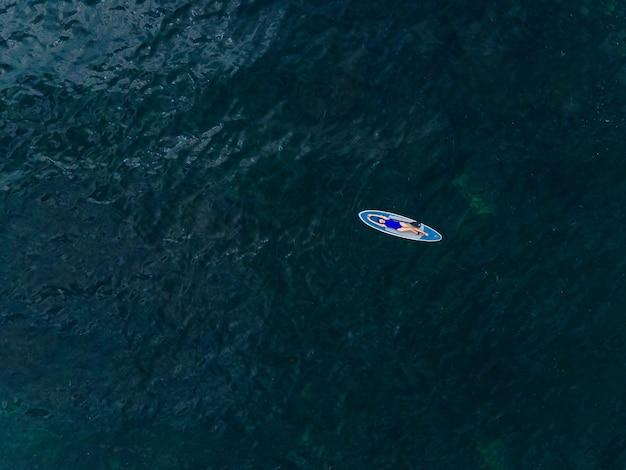 Женщина в синем купальнике лежит спиной на лодке с веслом далеко в море в летний день.