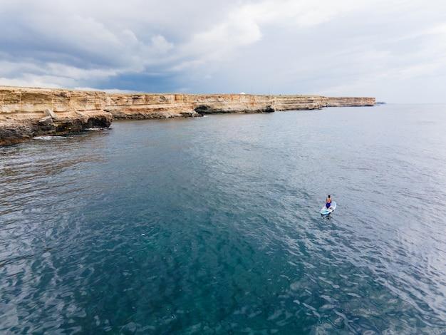 Женщина в синем купальнике сидит на берегу моря далеко от моря