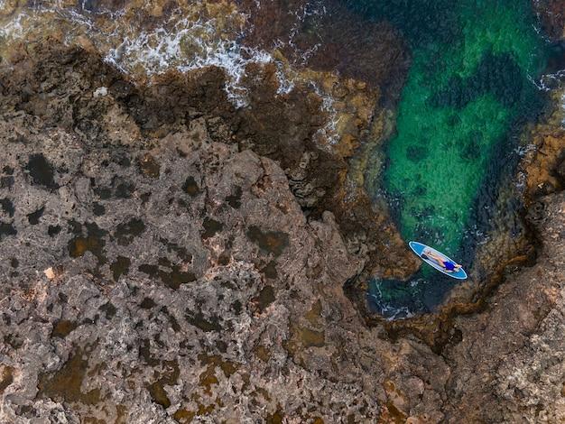 Женщина в синем купальнике сидит спиной на супе с веслом у скалы далеко от моря в летний день